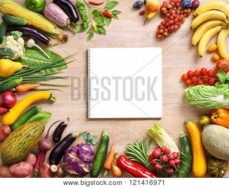 Fresh organic vegetables on a wooden background and notebook.