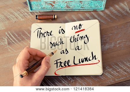 Retro effect and toned image of a woman hand writing a note with a fountain pen on a notebook. Handwritten text There Is No Such Thing As A Free Lunch as business concept image