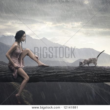 Young woman and cat on a trunk