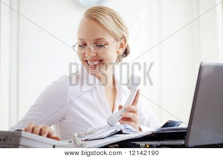 Portrait of a smiling business woman calling by telephone