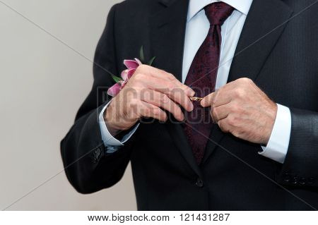 The groom wears a suit in front of a mirror. A man ties a tie.   An old groom preparing for the wedding. 