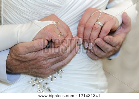 Hands of elderly bride and groom together. Old newlyweds. Wedding elderly men and women. Love all age are obedient.