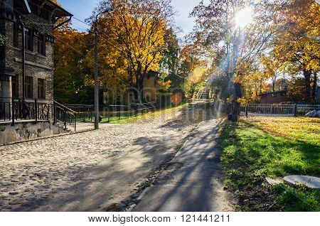 Sunny autumn street with stony road of Riga, Latvia