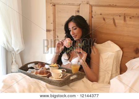 a beautiful woman with breakfast in bed
