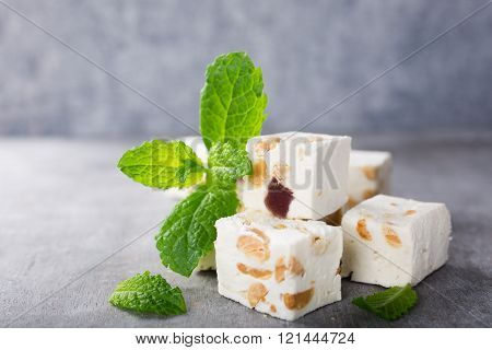 Soft nougat blocks with peanuts and fruit with fresh mint leaves on gray background with copy space. Holiday concept.