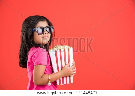 happy girl eating popcorn and wearing glasses, indian girl eating popcorn