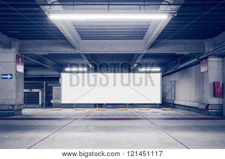 Parking garage underground interior with blank billboard