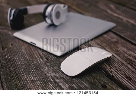 Tablet With Headphones And Mouse On A Wooden Background