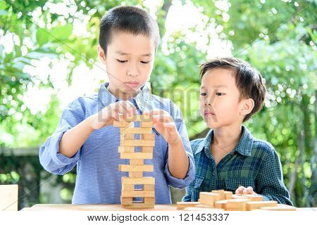 Two Boy Play Wooden Block Tower