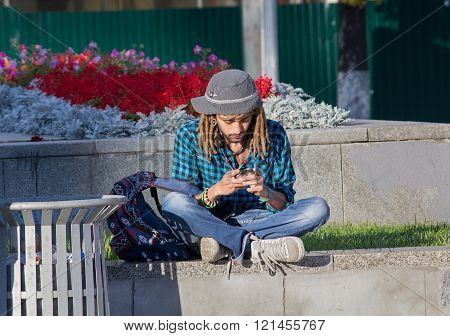 Kiev, Ukraine - September 09, 2015: Young Man With Dreadlocks Listening To Music While Sitting On Th