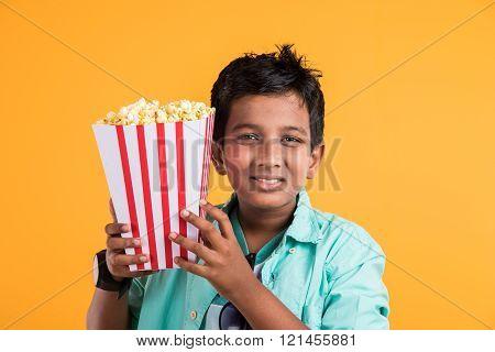 Joyful indian kid holding a big box of popcorn