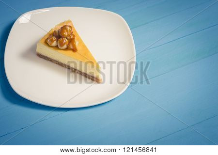 macadamia cheesecake topping with caramel on white plate on blue wood background,vintage toning