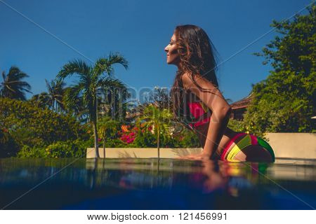 fashion outdoor photo of beautiful woman with dark hair relaxing  in swiming pool