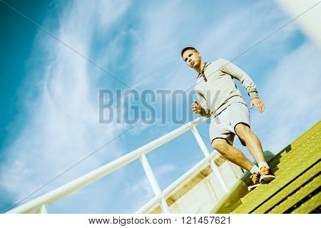 Man runner running on stairs in city sport training. Young male jogger athlete training and doing workout outdoors in city.
