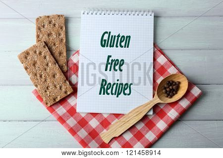 Open recipe book and text Gluten free recipes on wooden background