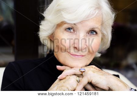 Beautiful senior woman sitting and smiling relaxed,  on dark background with crossing fingers
