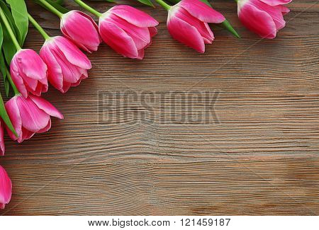 Fresh pink tulips on a wooden table, top view