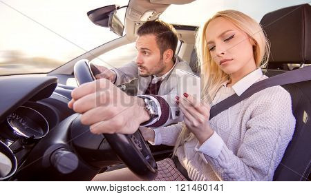 Woman using a smart phone while driving a car