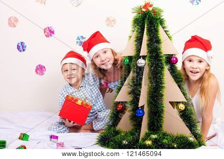Happy little smiling boy and two girls with christmas hat.