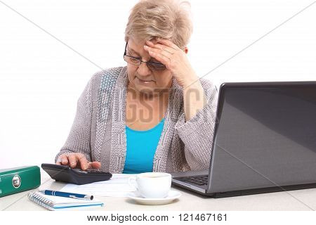 Worried elderly senior woman counting utility bills at her home, financial security in old age