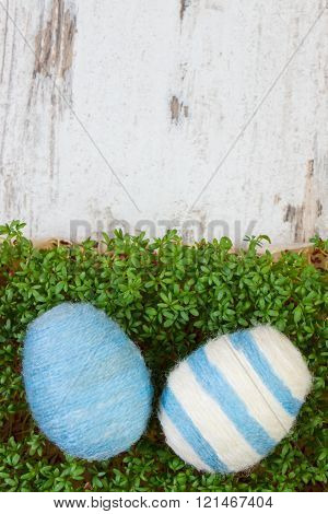 Easter eggs wrapped woolen string and green cress on wooden background, copy space for text, decorat