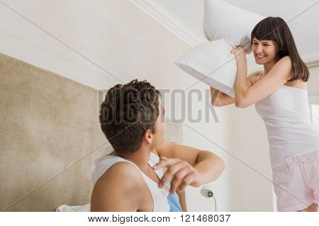 Woman playing pillow fight with man on bed in bedroom