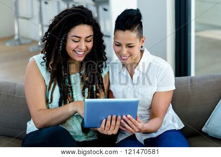 Lesbian couple using digital tablet in living room