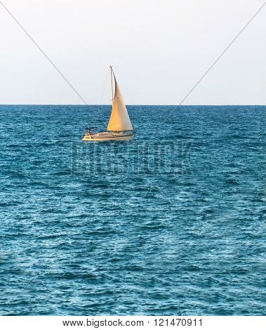 boat with a sail on the high seas