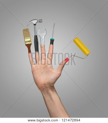 Hand with an open palm and tools instead of fingers on a gray background. Brush, hammer, wrench, scr