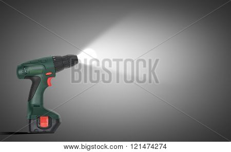 Green drill with shining bulb on grey background