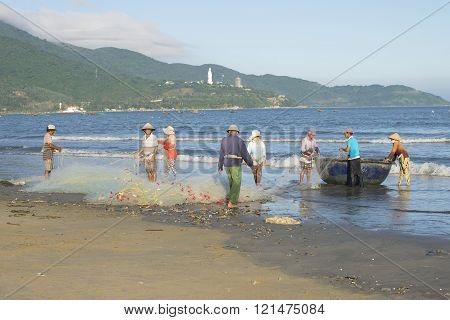 A group of fishermen dismantle the network before going fishing. Da Nang, Vietnam