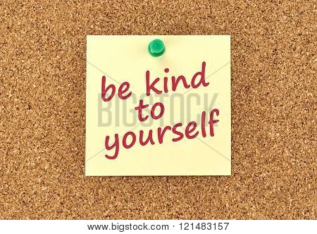 The phrase Be Kind To Yourself in red text on a yellow sticky note posted to a cork notice board.