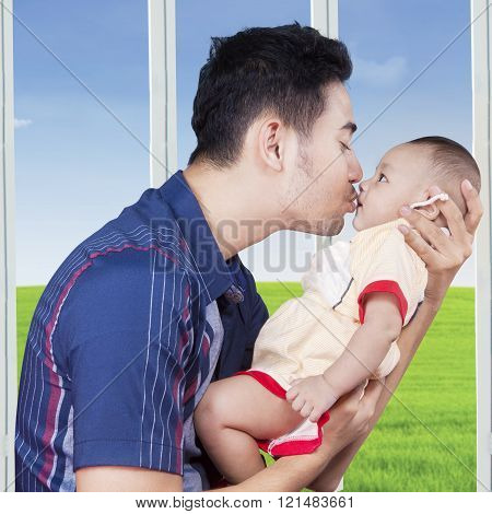 Portrait of young father holds a three months baby near the window and kiss the baby's lips