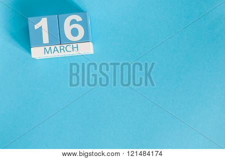 March 16th. Image of march 16 wooden color calendar on blue background.  Spring day, empty space for