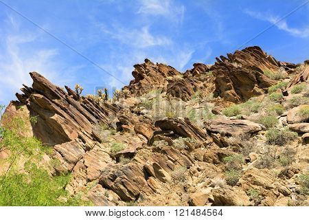 Scenic view of a rugged, rocky mountainside framed against a blue sky. Mo
