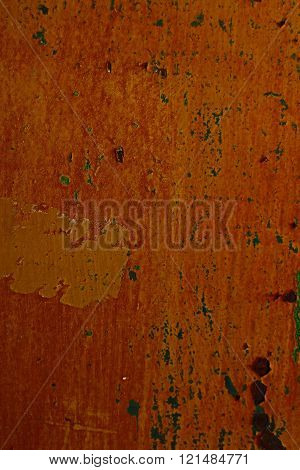 Weathered orange scrap metal close up with green paint flecks and grunge texture.