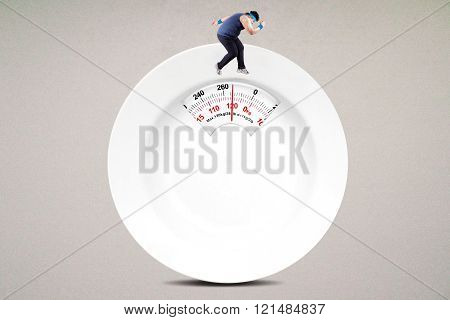 Obese man runs above scale shaped a plate