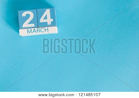 March 24th. Image of march 24 wooden color calendar on blue background.  Spring day, empty space for