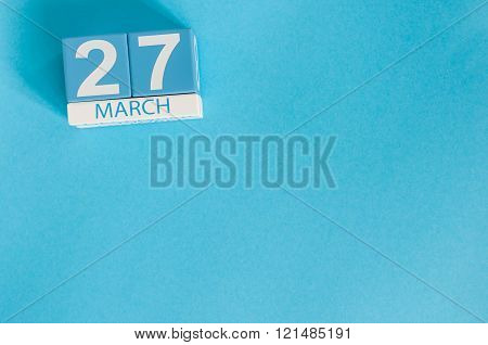 March 27th. Image of march 27 wooden color calendar on blue background.  Spring day, empty space for