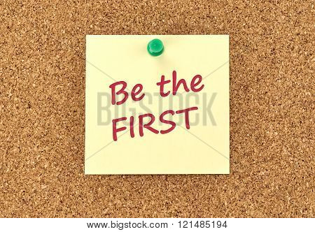 The phrase Be The First in red text on a yellow sticky note posted to a cork notice board.