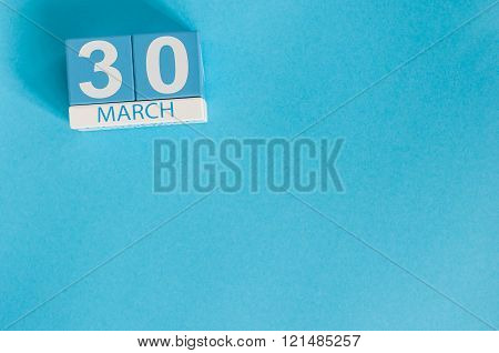 March 30th. Image of march 30 wooden color calendar on blue background.  Spring day, empty space for