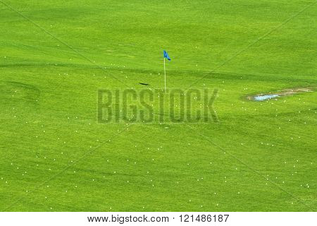 Early morning sunlight brings out the vibrant green colors of a golf course sprinkled with golf balls around a target flag