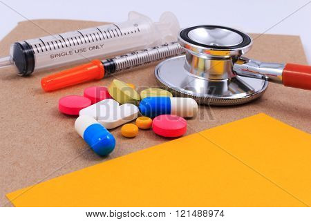 Red stethoscope, syringes, sticky note and many colorful pills on brown craft paper background.