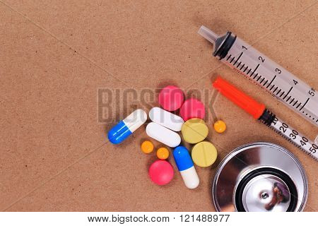 Red stethoscope, syringes and many colorful pills on brown craft paper background.