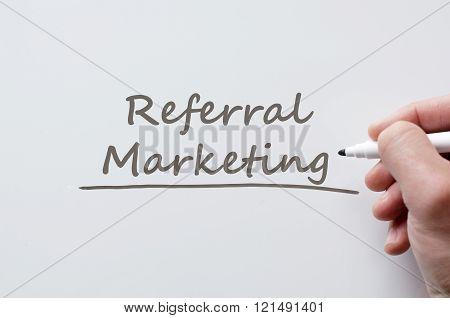 Human hand writing referral marketing on whiteboard