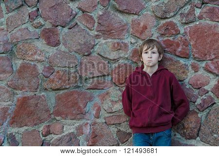Teenage boy wearing burgundy hooded sweatshirt with vertical zipper leaning red granite boulders wal