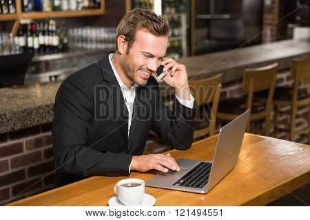 Thoughtful man using laptop and having a phone call in a pub