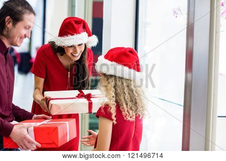 Happy parents giving Christmas gifts to their daughter in shopping mall