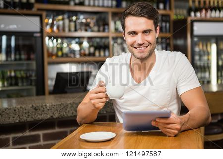 Handsome man using tablet and having coffee in a pub
