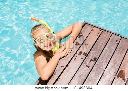 Portrait of happy woman with snorkel gear leaning on pool side on a sunny day